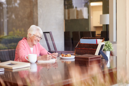 Senior Woman Writing Memoirs In Book At Desk