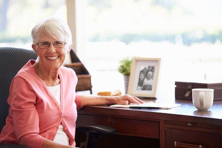 adult 80s: Senior Woman Writing Memoirs In Book At Desk