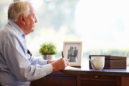 writing book: Senior Man Writing Memoirs In Book Sitting At Desk Stock Photo