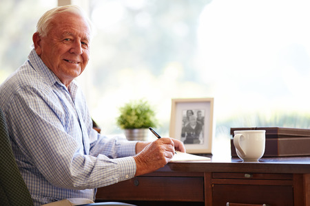 Senior Man Writing Memoirs In Book Sitting At Desk Imagens