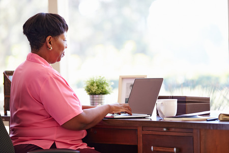 home office desk: Mature Woman Using Laptop On Desk At Home Stock Photo
