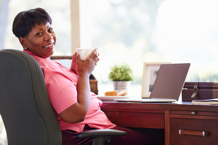 Mature Woman Using Laptop On Desk At Home Stock Photo