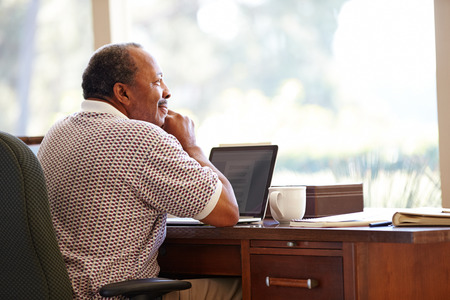 african american male: Senior Man Using Laptop On Desk At Home Stock Photo
