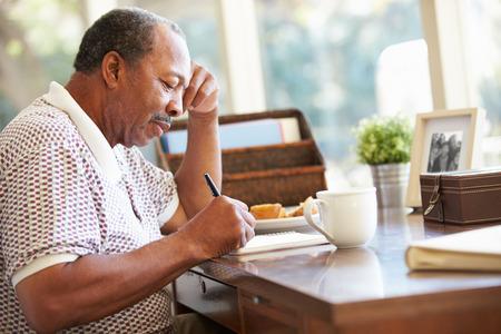 Senior Man Writing Memoirs In Book Sitting At Desk Foto de archivo