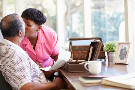 Senior Couple Putting Letter Into Keepsake Box photo