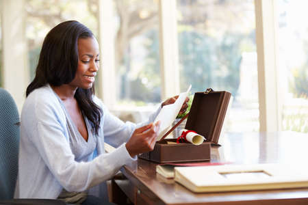 Woman Looking At Letter In Keepsake Box On Desk photo