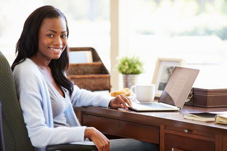 femme assise: Femme Utiliser un ordinateur portable sur le bureau � la maison