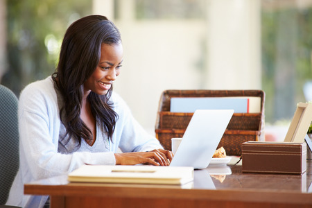 trabjando en casa: Mujer que usa la computadora portátil en el escritorio en casa
