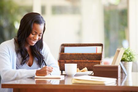 notebook: Vrouw schrijven in notebook Zit Aan Bureau