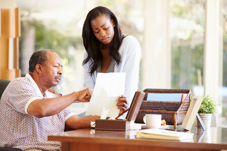 Senior Father Discussing Document With Adult Daughter photo