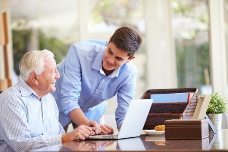 personas ayudando: Nieto adolescente Abuelo de ayuda con el ordenador portátil