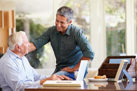 El hijo adulto de ayuda del hijo con la computadora portátil