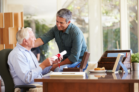 adult offspring: Senior Father Discussing Document With Adult Son Stock Photo