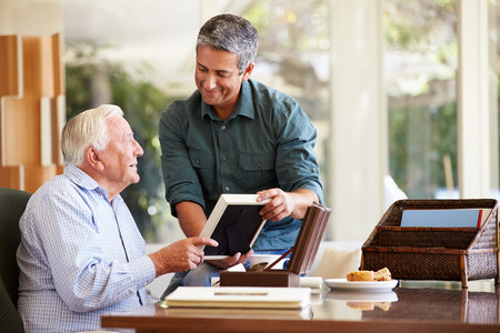 adult 80s: Senior Father Looking At Photo In Frame With Adult Son
