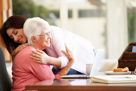 Senior Mother Being Comforted By Adult Daughter photo