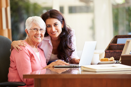 working mother: Adult Daughter Helping Mother With Laptop Stock Photo