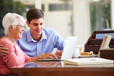 grandmother and grandson: Teenage Grandson Helping Grandmother With Laptop