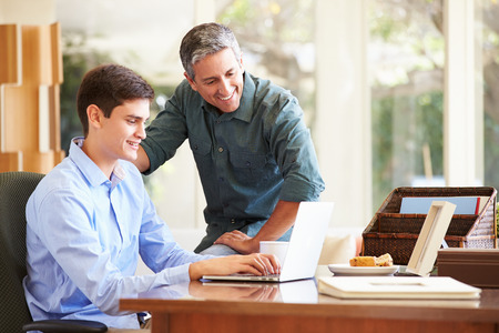 Father And Teenage Son Looking At Laptop Together photo