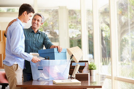 Father Helping Teenage Son Pack For College Stockfoto