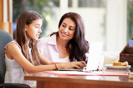 madre e hija adolescente: Madre e hija adolescente que miran la computadora portátil Juntos Foto de archivo