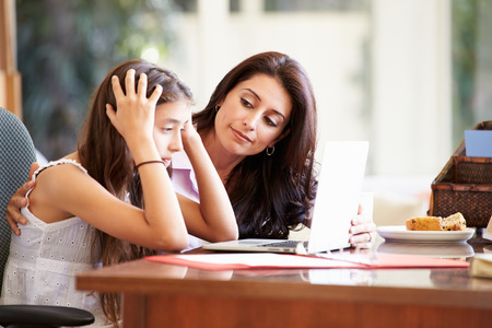mother and teen daughter: Mother Helping Stressed Teenage Daughter Looking At Laptop Stock Photo