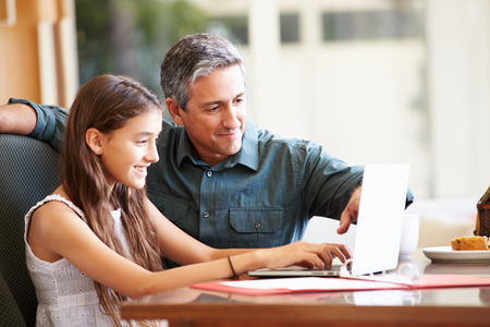 happy teenagers: Father And Teenage Daughter Looking At Laptop Together