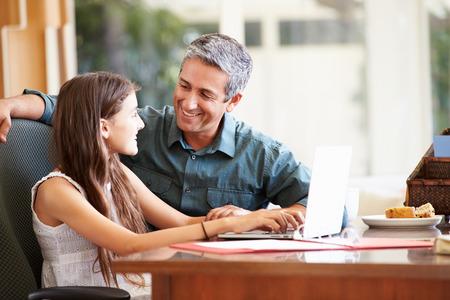 父と一緒にノート パソコンを見ての十代の娘