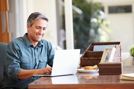 trabajando en casa: Hombre hispano maduro usando la computadora port�til en el escritorio en el hogar