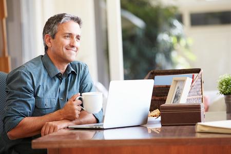 trabjando en casa: Hombre hispano maduro usando la computadora portátil en el escritorio en el hogar