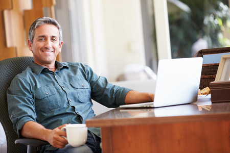 man with camera: Mature Hispanic Man Using Laptop On Desk At Home