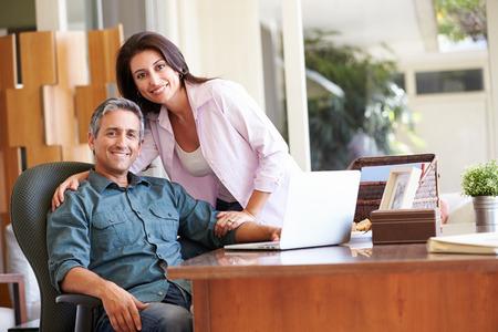 hispanic: Hispanic Couple Using Laptop On Desk At Home
