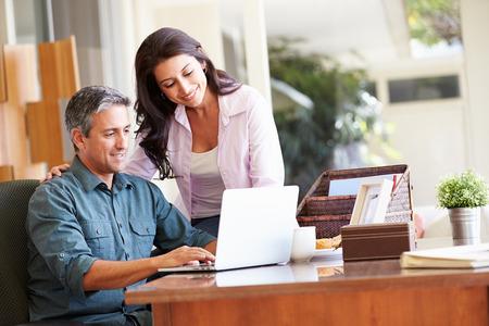 trabajando en casa: Pareja hispana Usar el port�til en el escritorio en el hogar