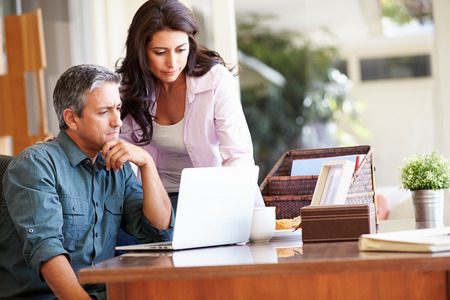 contemplate: Worried Hispanic Couple Using Laptop On Desk At Home Stock Photo