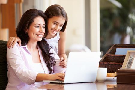 Mutter und jugendliche Tochter, die zusammen Laptop Standard-Bild - 31067065