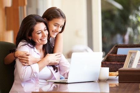 madre trabajando: Madre e hija adolescente que miran la computadora port�til Juntos Foto de archivo