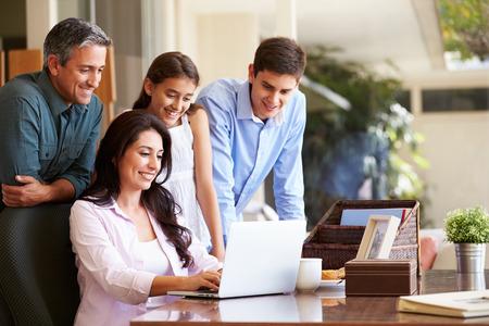 working at home: Familia miran la computadora port�til Juntos