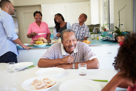 Multi-Generation Family Preparing For Meal At Home Stock Photo