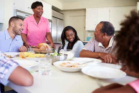 Multi-Generation Family Sitting Around Table Eating Meal photo