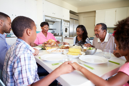 family praying: Familia multi-generacional que dice rezo antes de comer comidas Foto de archivo