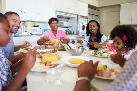 Familia multi-generacional sentado en la mesa que come una comida