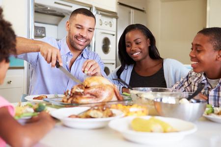 Rodina sedí kolem stolu v Home Eating Meal