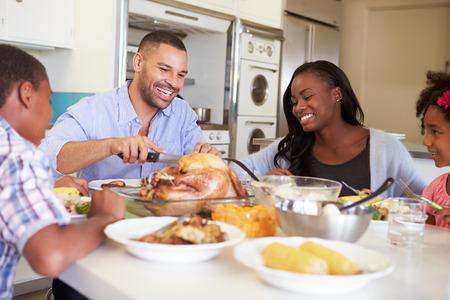 Familia que se sienta alrededor de la mesa en casa comiendo comidas Foto de archivo
