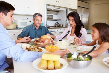 mujer orando: Familia que se sienta alrededor de la mesa que dice rezo antes de comer comidas Foto de archivo