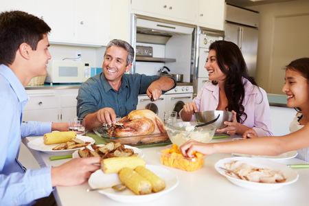 Familia que se sienta alrededor de la mesa en casa comiendo comidas Foto de archivo - 31066942