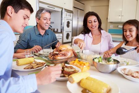 familia comiendo: Familia que se sienta alrededor de la mesa en casa comiendo comidas Foto de archivo