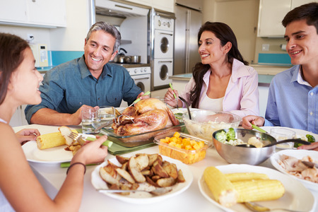 family eating: Familia que se sienta alrededor de la mesa en casa comiendo comidas Foto de archivo