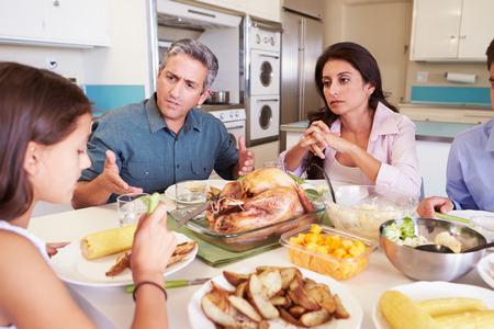 Familie die Argument zitten rond de tafel eten Maaltijd
