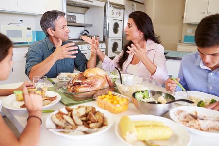argumento: Familia tienen argumento sentado en la mesa que come una comida