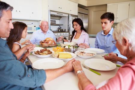 mujeres orando: Familia multi-generacional que dice rezo antes de comer comidas Foto de archivo