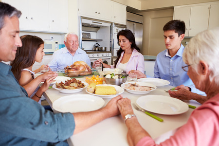 praying: Multi-Generation Family Saying Prayer Before Eating Meal